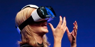 British television presenter Rachel Riley shows a virtual-reality headset called Gear VR during an unpacked event of Samsung ahead of the consumer electronic fair IFA in Berlin, Wednesday, Sept. 3, 2014. (AP Photo/Markus Schreiber)